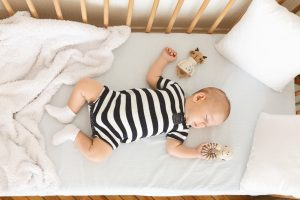 Newborn baby sleeping in wooden bed and holding his toy
