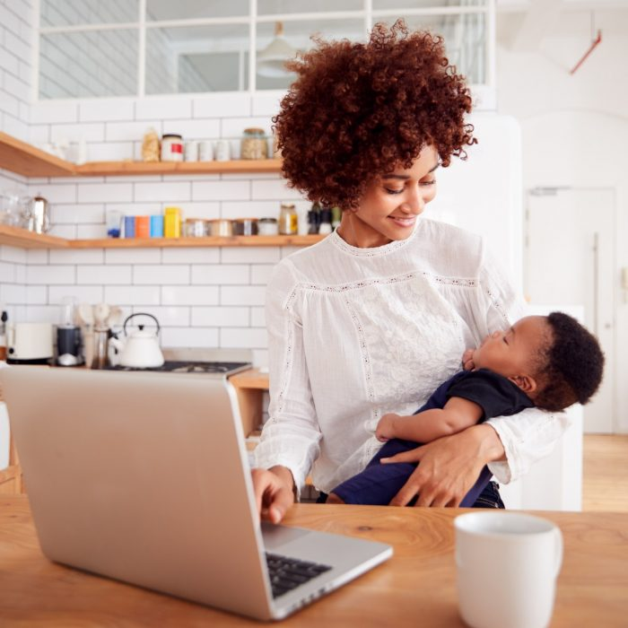 Multi-Tasking Mother Holds Sleeping Baby Son And Works On Laptop Computer In Kitchen